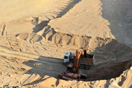 Excavator loading sand into a dump truck, top view. The work of heavy industrial machinery in the opencast mining quarry - Image