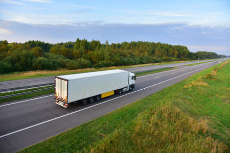 White truck with semi-trailer driving along highway on the sunset background. Goods delivery by roads. Services and Transport logistics. Object in motion, soft focus.