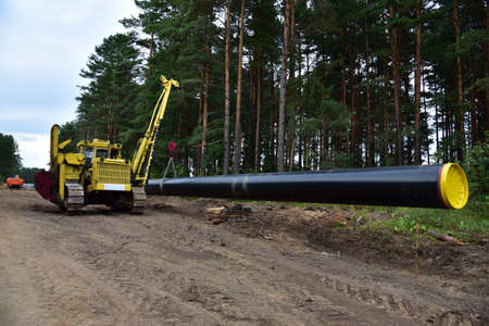 Natural gas pipeline construction work in forest area. Installation of gas and crude oil pipes. Pipe on top of wooden supports at construction site. Construction of gas pipes to new LNG plant