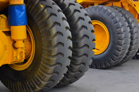 Tires with rims and electric motor-wheels engines of a yellow career dump trucks, mining trucks.
