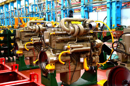 Diesel engines with huge turbines on assembly line in the workshop of the factory for the production of large mining trucks. Warning, small roughness sharpness, possible granularity. Stockfoto