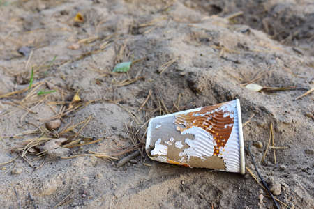 Discarded Paper coffee cup on ground. Disposable coffee cup on sand. The problem of environmental pollution. Pile of abandoned garbage, including food waste, fast food packaging