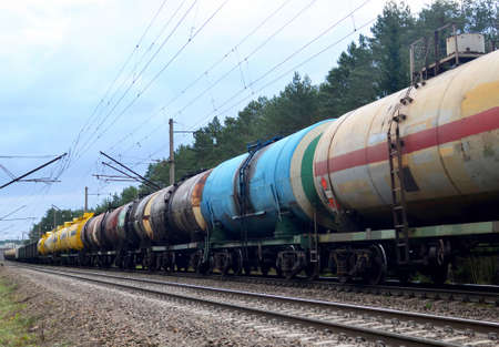 Freight train with petroleum tank cars on railroad. Rail cars carry oil and ethanol. Railway logistics explosive cargo. Transportation of methanol, crude and gas.Petrochemical tank cars