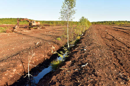 Landscape on peatlands where being development of the peat. Drainage of peat bogs at extraction site. Drilling on bog for oil exploration. Wetlands declining and under threat. Imagens