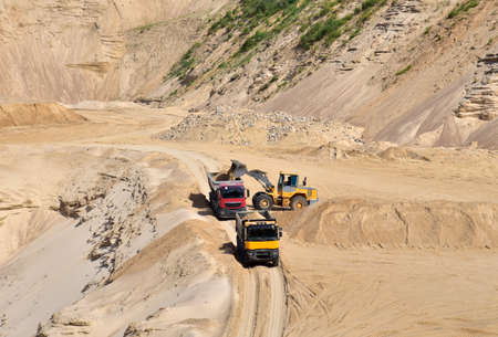 Wheel front-end loader loading sand into heavy dump truck at the opencast mining quarry. Dump truck transports sand in open pit mine. Quarry in which sand and gravel is excavated from the ground. Standard-Bild
