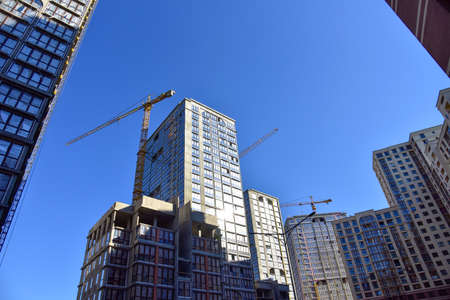 Tower cranes working at construction site on blue sky background. Construction process of the new modern residential buildings. Installing double glazed windows in building Standard-Bild
