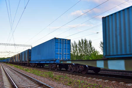 Cargo Containers Transportation On Freight Train By Railway. Intermodal Container On Train Car. Rail Freight Shipping Logistics Concept. Soft focus, possible granularity. Object in motion