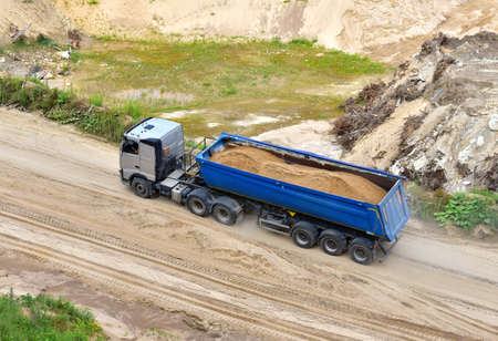 Truck with tipper semi trailer transported sand from the quarry. Dump truck working in open pit mine. Sand and gravel is excavated from ground. Mining industry