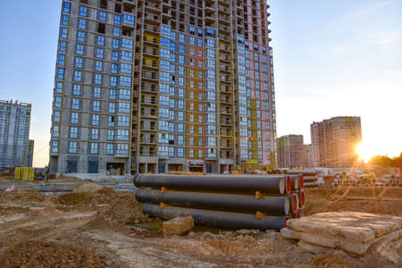 View on large construction site with tower cranes and buildings on sunset background. Concrete sewer pipes for laying an external sewage system at a construction site. Sanitary drainage system