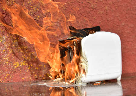 Burning toaster. Toaster with toast caught on fire over table.