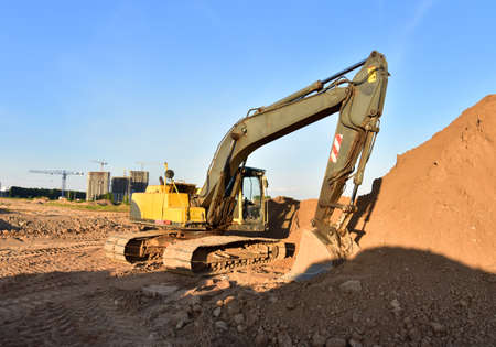 Excavator works on a construction site during excavation work against a blue sky background. Open pit development for sand extraction
