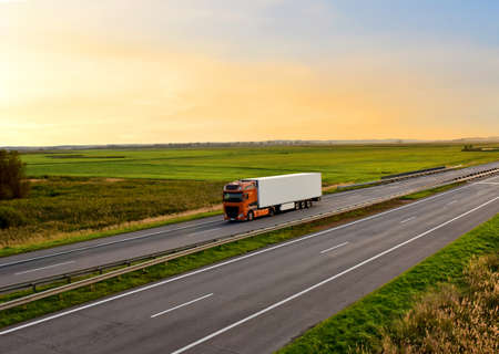 Truck with semi-trailer driving along highway on the sunset background. Goods delivery by roads. Services and Transport logistics. Modern Lorry Transport concept. Long Self-driving lorries