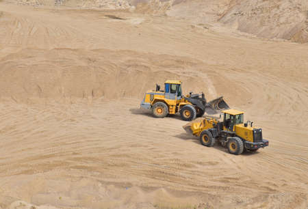 Wheel loader working at the sand open pit. Quarry in which sand and gravel is excavated from the ground. Mining industry. 免版税图像
