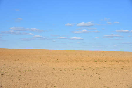 View of a deserted sand field against a blue sky with clouds.