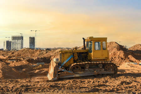 Dozer on earthmoving at construction site on sunset background. Construction machinery and equipment on groundwork. Bulldozer leveling ground for new road construction. Tower cranes in action 免版税图像