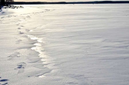 Structure of snow and ice on frozen lake. Winter landscape concept. Frozen river surface view in winter time