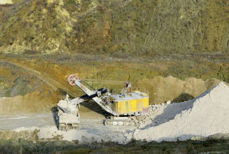 Excavator in quarry loads rock into a mining truck. Excavators and trucks work in a chalk open pit. Aerial top view of mining canyon with mountains and rocks.