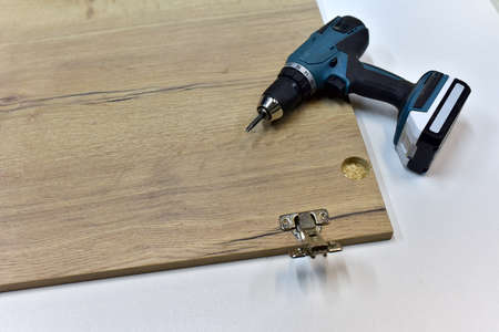 Cordless combi drill for assembly the furniture door hinges ot he wooden furniture made of particle board. Medium Density Fiberboard (MDF). Woodworking industry and furniture assembly concept