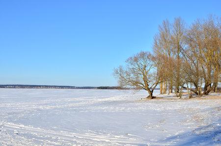 Winter scene of frozen lake on blue sky background. Snowy river view
