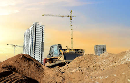 Dozer on earthmoving at construction site on sunset background. Construction machinery and equipment on groundwork. Bulldozer leveling ground for new road construction. Tower cranes in action Standard-Bild