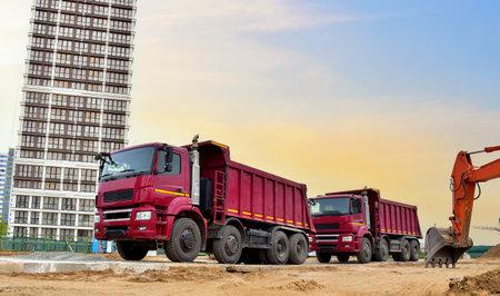 Dump truck and excavator working on earthworks at construction site on sunset background. Trucks for transportation of bulk cargo. Trucking industry, freight cargo transport concept Standard-Bild