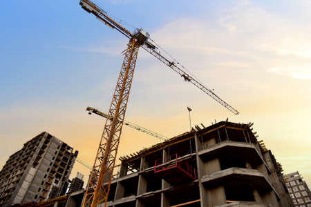 Tower crane in action at construction site on blue sky background. Crane the build the high-rise building. New residential skyscraper. Tall house renovation project, government programs Standard-Bild