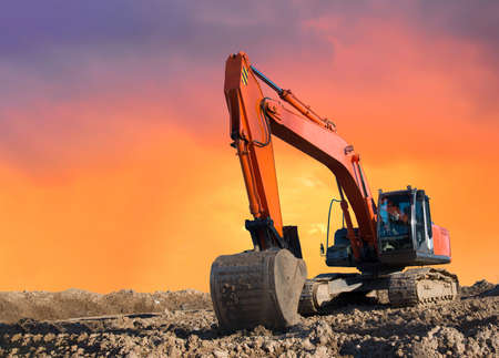 Excavator working on earthmoving at open pit mining on amazing sunset background. Backhoe digs sand and gravel in quarry. Heavy construction equipment during excavation at construction site