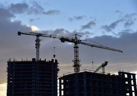 Silhouettes of tower cranes on awesome sunset background. Preparing to pour a bucket of concrete into formwork. Construction a multi-storey residential building. Small sharpness, possible granularity