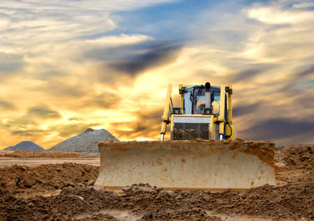 Dozer on earthmoving at construction site on awesome sunset background. Construction machinery and earthmoving equipment on groundwork. Bulldozer leveling ground for new road construction