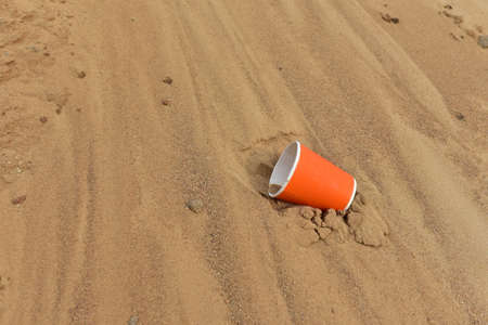 Discarded Paper coffee cup on sand at beach. Disposable coffee cup on sandy background. The problem of environmental pollution. Pile of abandoned garbage, including food waste, fast food packaging