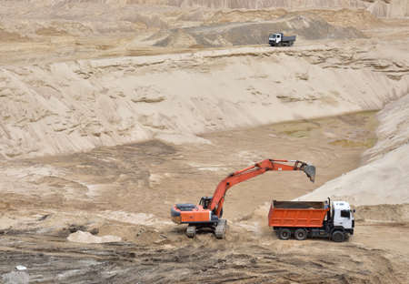 Excavator load the sand into dump truck in open-pit mining. Developing the sand in the opencast, processing of loose material. Heavy machinery on groundworks quarry. Earthworks contract 免版税图像