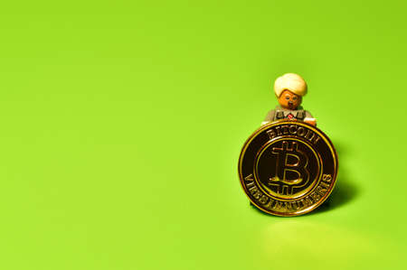 Bitcoin coin in the hands of a lego minifigure a Donald Tram or Biden. Gold crypto coin and cryptocurrency investing concept. Blockchain and financial technology. Exchange market trading price chart