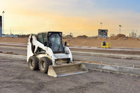 Skid-steer loader for loading and unloading works on city streets. Compact construction equipment for work in limited conditions. Road repair at construction site 免版税图像