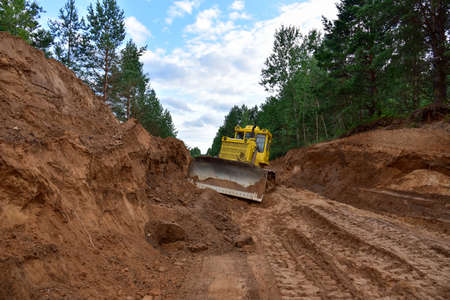 Dozer during clearing forest for construction new road. Yellow Bulldozer at forestry work Earth-moving equipment at road work, land clearing, grading, pool excavation, utility trenching
