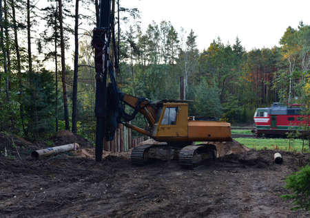 Vibrating hydraulic hammer in forest area. Hydraulically driven free-fall hammer for impact driving of steel pipes. Laying pipes underground through the railroad. Piling for deep foundation