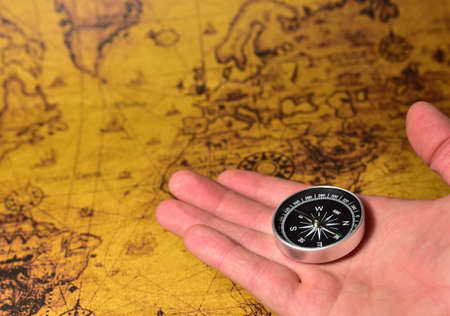 Compass in hand on map. Tourist compass for orientation on the terrain. Magnetic declination сalculator. Historical explorer help. Map reading and land navigation concept. Orient on maps