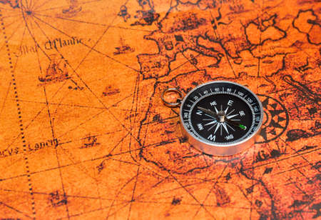 Compass on map. Tourist compass for orientation on the terrain. Magnetic declination сalculator. Historical explorer help. Map reading and land navigation concept. Orient on maps