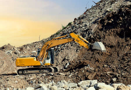 Recycling concrete and construction waste from demolition. Excavator at landfill of the disposa. Reuse of building rubble. Backhoe dig gravel at mining quarry on sunset background. Concrete debris