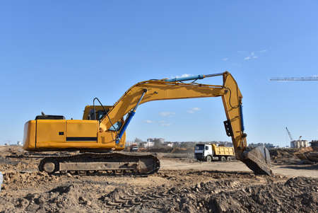 Excavator on earthworks at construction site. Backhoe on foundation work and road construction. Heavy machinery and construction equipment Foto de archivo