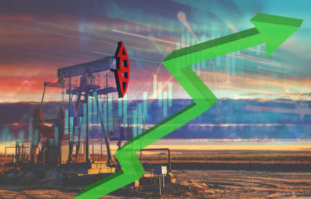 Crude mining concept and graph of falling oil prices on the trading exchange. Crude oil pump jack at oilfield on sunset backround. Fossil crude output and fuels oil production. Oil drill rig
