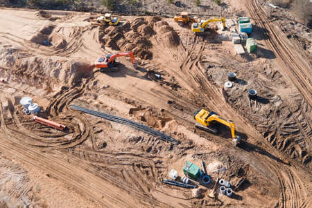 Installation of storm sewers and construction of a road in a new residential area. Excavator on earthworks, view from the top, view from the drone. Roadworks soil compactor