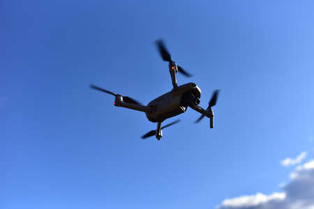 Drone flying in the air on blue sky background. Quadcopter with HD video and a 48MP Camera 4K Video during flight. Copter for photography and 8K video recording. Unmanned aerial vehicle (UAV)