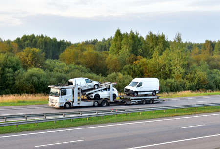Car carrier trailer transports cars on highway on sunset background. Auto transport and car shipping services concept. Truck with Semi-remorque. Cars Shipping Foto de archivo
