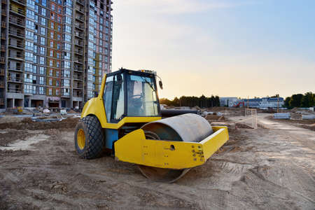 Vibro Roller Soil Compactor leveling ground at construction site. Vibration single-cylinder road roller on construction road. Road work for new asphalt laying. Tower cranes build high-rise buildings Фото со стока