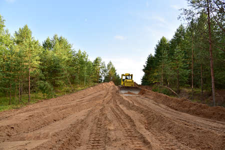 Dozer during clearing forest for construction new road. Yellow Bulldozer at forestry work Earth-moving equipment at road work, land clearing, grading, pool excavation, utility trenching Banque d'images