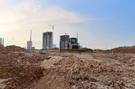 Dozer on earthmoving at construction site on sunset background. Construction machinery and equipment on groundwork. Bulldozer leveling ground for new road construction. Tower cranes in action Фото со стока
