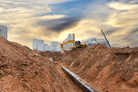 Excavator at construction site during laying sewer and main reticulation systems. Civil infrastructure pipe, water lines, sanitary sewers and storm sewers. Underground utilities installation