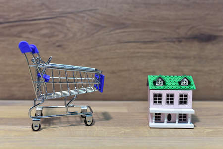 House and Supermarket Trolley. Home buying or selling. Building on credit housing or renting an apartment. Home in shopping cart for family. Real Estate Investing and Housing Market. American dream