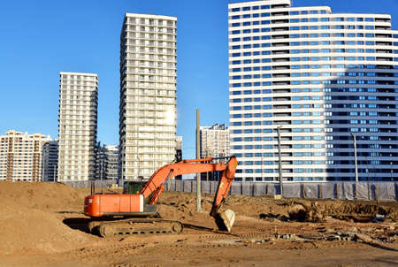 View of a large construction site. Construction of buildings and multi-storey residential homes. Excovator for excavation work when digging a foundation pit. Building under construct Фото со стока