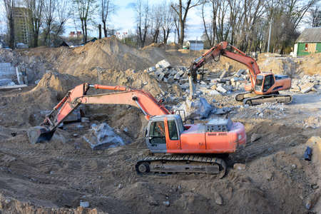 Excavator with hydraulic breaker hammer. Excavator on demolition the old building. Destruction of concrete and hard rock. Recycling of construction waste at the construction site. Jackhammer using